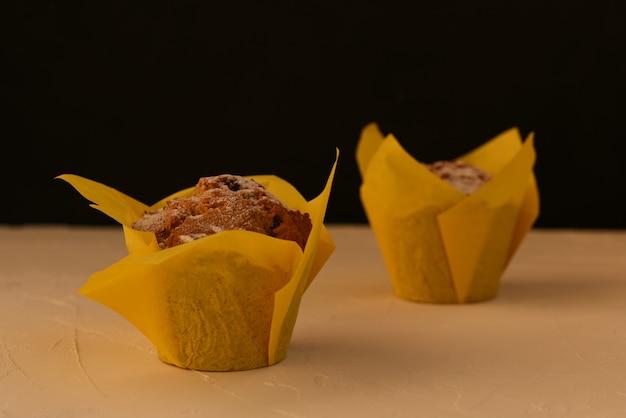 Twee muffins met rozijnen in een geleipapier voor het bakken staan diagonaal op een witte tafel