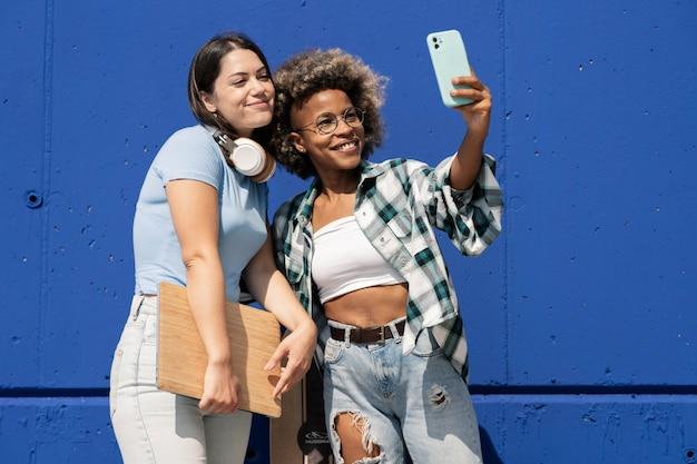 Twee multi-etnische vrienden nemen selfie, met koptelefoon en laptop, op een blauwe muur