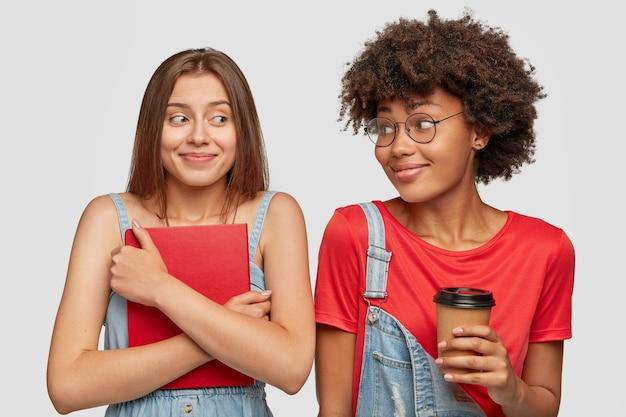 Twee multi-etnische vrouwelijke studenten hebben blije uitdrukkingen na de lessen, drinken afhaalkoffie, houden een boek vast, bereiden zich samen voor op examens, hebben oprechte vriendschap. mensen, jongeren, studeren