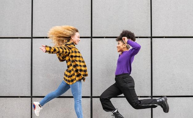 Twee multiraciale vrouwen die met een muur op de achtergrond springen Premium Foto