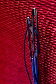 Twee naalden met blauwe draad op een achtergrond van rode stof. detailopname.