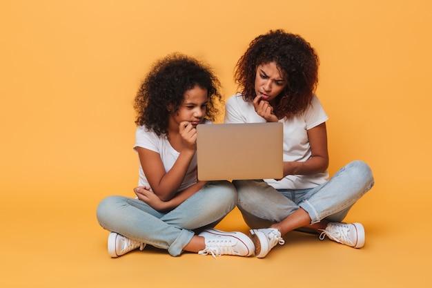 Twee nadenkende afro-amerikaanse zusters die laptop computer met behulp van