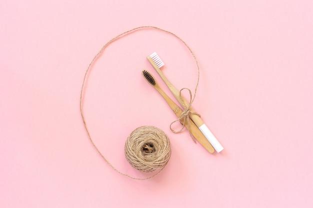 Twee natuurlijke milieuvriendelijke bamboeborstels met witte en zwarte borstelharen, gebonden met touw op roze achtergrond