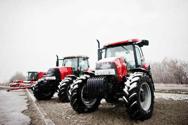 Twee nieuw rood tractorverblijf bij sneeuwweer combaine