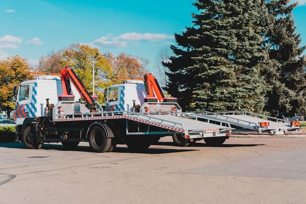 Twee nieuwe sleepwagens geparkeerd dichtbij de weg in de stad. kranen op vrachtwagen voor het slepen van auto's. stedelijk. onderhoud. zijaanzicht. tows met lifters