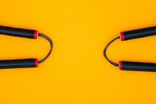 Twee nunchats op een oranje oppervlak