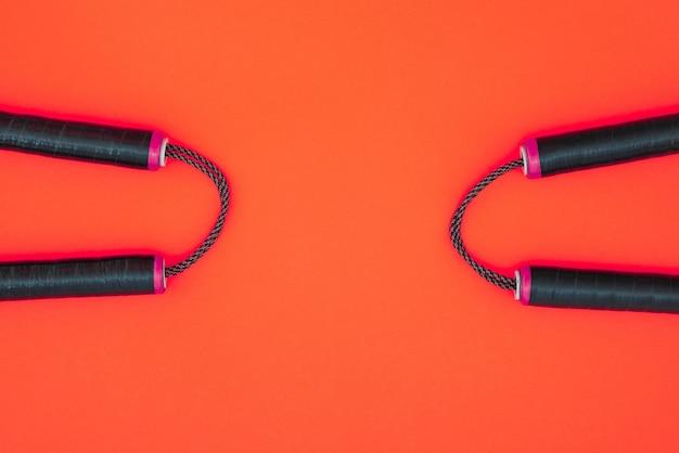 Twee nunchats op een rode ondergrond