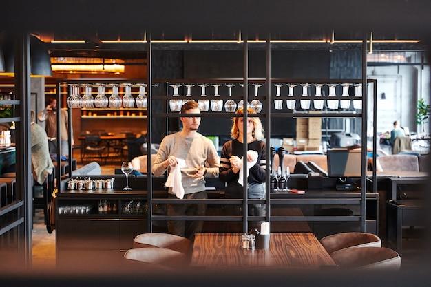 Twee obers wrijven glazen aan de bar, restaurant in moderne stijl