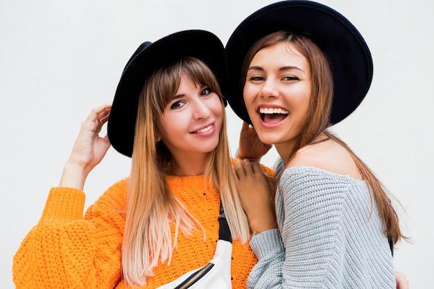 Twee onbezorgde meisjes die luchtkus verzenden naar camera die zich op wit bevindt
