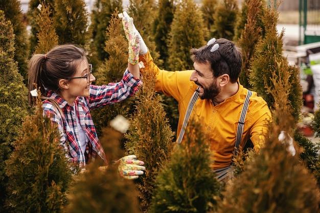 Twee ondernemers gehurkt omringd door groenblijvende bomen en geven elkaar een high five.