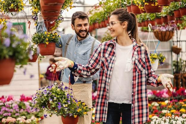 Twee ondernemers houden potten met bloemen vast en vertellen het. kwekerij interieur.