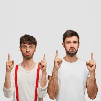 Twee ongelukkige, bebaarde jonge jongens hebben een ontevreden uitdrukking, wijs met beide wijsvingers naar boven
