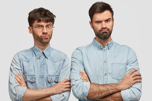 Twee ontevreden ongeschoren mannen houden hun handen gekruist, gekleed in spijkerjasjes