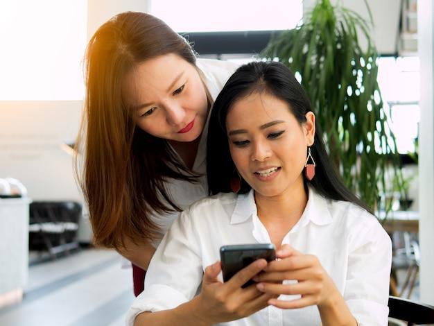 Twee ontspannen ontspannen jonge aziatische vrouwen kijkend op het scherm in slimme telefoon, smartphone c