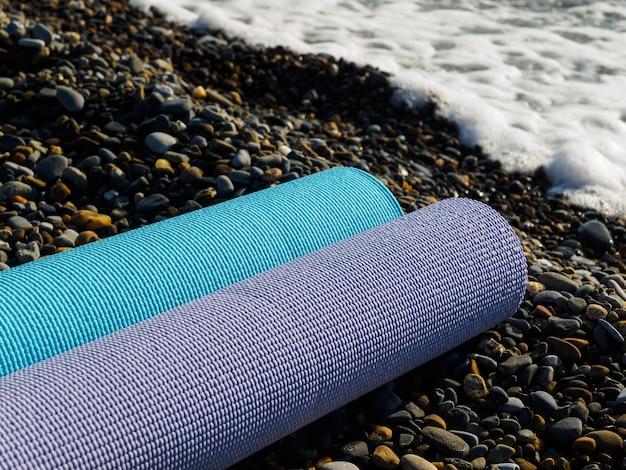 Twee opgerolde tapijten in verschillende kleuren op de rotsachtige kust van de zwarte zee