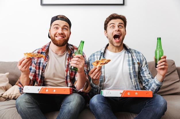 Twee opgewonden emotionele mannen die pizza eten en bier drinken, terwijl ze thuis het voetbalteam steunen