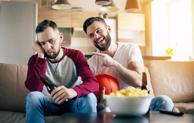 Twee opgewonden grappige jonge vrienden fans van basketbal kijken naar tv-wedstrijd en schreeuwen terwijl ze op de bank rusten