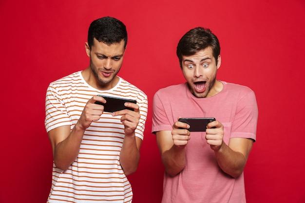 Twee opgewonden jonge mannen die zich geïsoleerd over rode muur bevinden, spelen op mobiele telefoon