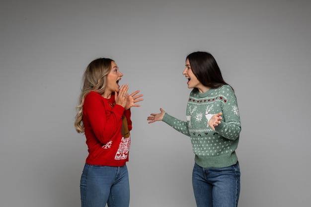 Twee opgewonden jonge meisjesvrienden in wintertruien die iets bespreken met emoties op een grijze achtergrond
