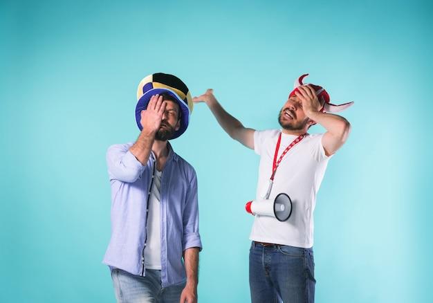 Twee opgewonden mannelijke vrienden vieren het kijken naar sport op televisie met megafoon over blauwe studio