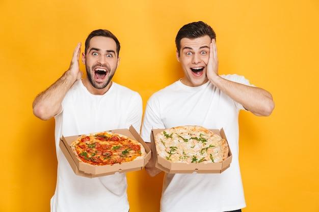 Twee opgewonden mannen, vrijgezellen van 30 jaar in witte t-shirts die glimlachen en pizzadozen vasthouden terwijl ze geïsoleerd over een gele muur staan