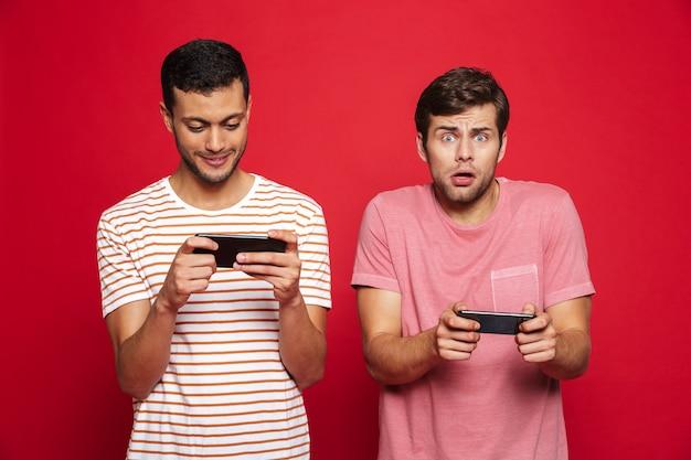 Twee opgewonden mannenvrienden die zich geïsoleerd over rode muur bevinden, spelen op mobiele telefoons