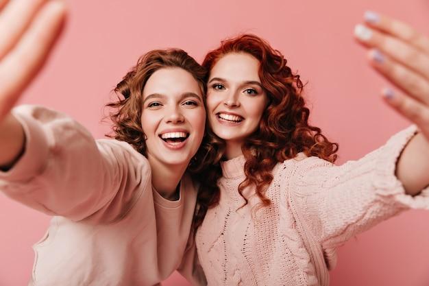 Twee opgewonden meisjes die samen plezier hebben. schattige jonge dames gebaren op roze achtergrond.