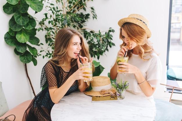 Twee opgewonden meisjes zitten aan de tafel met strooien hoed erop en praten over iets grappigs
