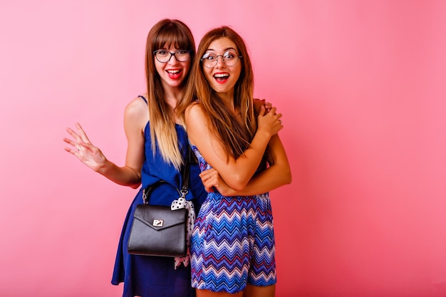 Twee opgewonden mooie vrouwen poseren voor een roze muur, gekleed in bijpassende marineblauwe elegante outfits en accessoires, positieve emoties, gelukkig samen.