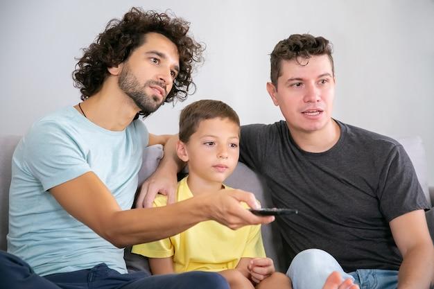 Twee opgewonden vaders en zoon kijken naar tv-show thuis, zittend op de bank in de woonkamer, knuffelen, met behulp van de afstandsbediening, wegkijken. familie- en home entertainment-concept