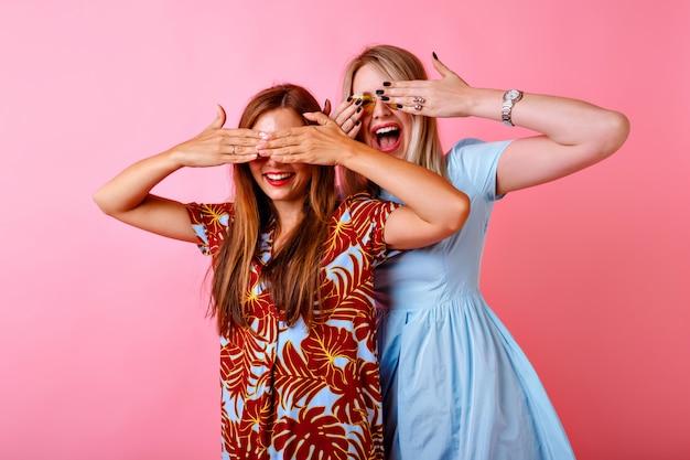 Twee opgewonden vrouwen glimlachen en sluiten hun ogen met de handen, gekleed in kleurrijke jurken