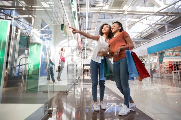 Twee opgewonden zwarte meisjes richten op winkelvenster