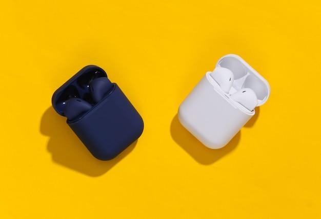 Twee oplaadcassettes met echte draadloze bluetooth-hoofdtelefoons of oordopjes op felgele achtergrond.