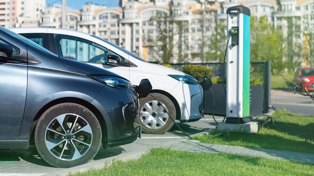 Twee opladen elektrische auto's bij laadstation in de stad