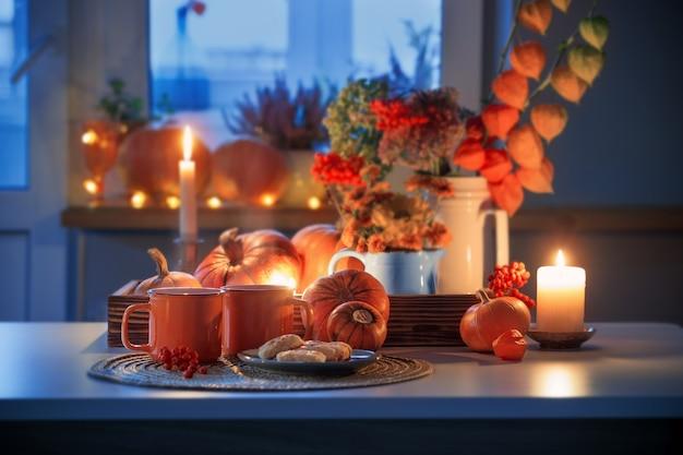 Twee oranje kopjes thee en herfstdecor met pompoenen, bloemen en brandende kaarsen op tafel