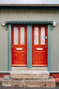 Twee oranje toegangsdeuren met glas en gordijnen in een blauwe deuropening