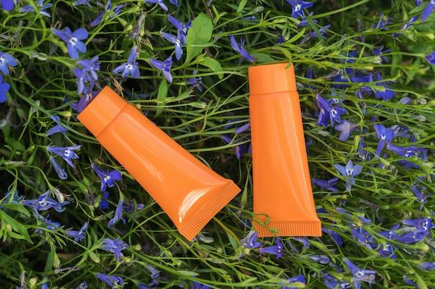 Twee oranje tubes crème op een bloeiende zomerachtergrond.