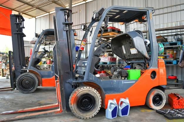 Twee oranje vorkheftrucks in reparatie werkplaats geparkeerd