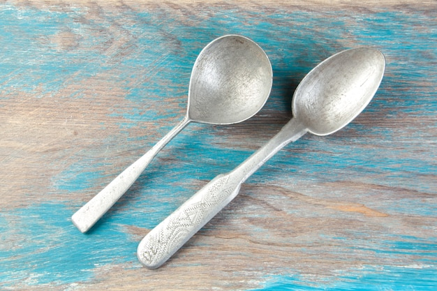 Twee oude aluminium lepels op blauwe houten achtergrond. kopieer ruimte voor tekst, rekwisieten voor voedselfotografie.