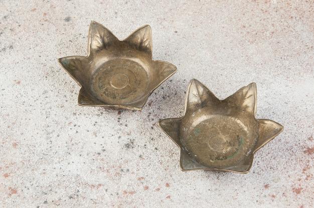 Twee oude bronzen kandelaars op betonnen ondergrond. ruimte voor tekst kopiëren.