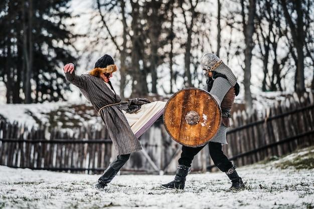 Twee oude krijgers in harnas met wapens vechten met zwaarden in de sneeuw