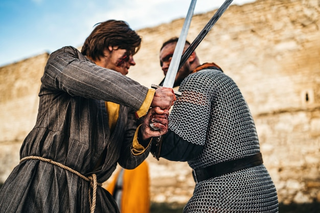 Twee oude krijgers in harnas met wapens vechten met zwaarden
