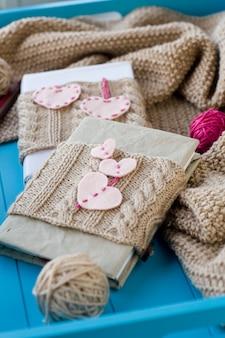 Twee oude kussens in gebreide hoes met vilten harten liggen naast de spoel, heldere filamenten en deken gebreid op blauwe tafel
