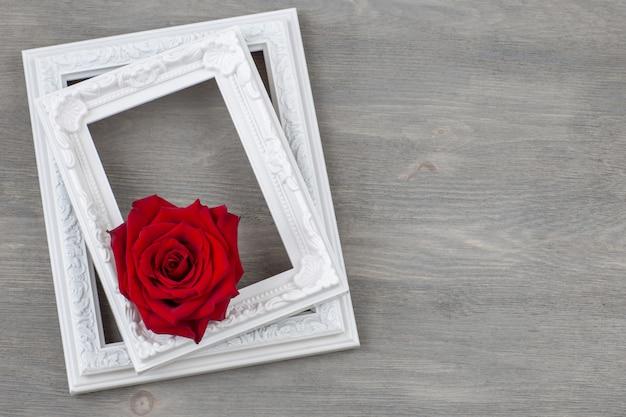 Twee oude lijsten en een rode rozenknop