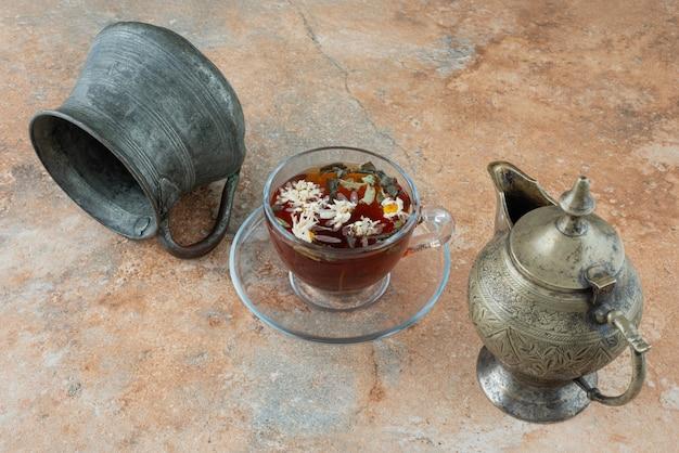 Twee oude theepotten met kruidenthee op marmeren achtergrond