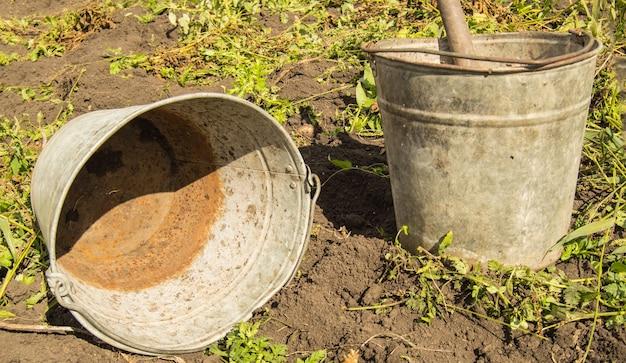 Twee oude, vuile, roestige, ijzeren emmers met vuile binnenkant en buitenkant liggen op de grond.