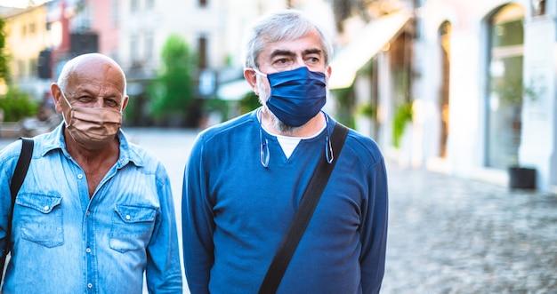 Twee oudere burgers lopen in de straat van de spookstad in de pandemische tijd