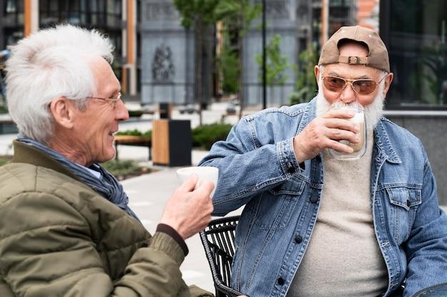 Twee oudere mannen in de stad die samen koffie drinken en kletsen
