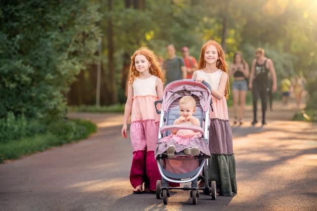 Twee oudere roodharige zussen lopen op een zonnige zomeravond in het park. met een kinderwagen met haar zusje. meisjes in lange vintage jurken rollen kinderwagen over het pad