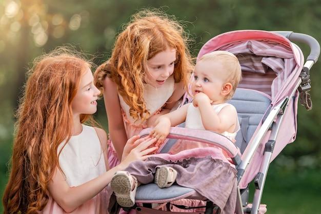 Twee oudere roodharige zussen lopen op een zonnige zomerdag met een kinderwagen in het park met hun jongere zus. de meisjes proberen het griezelige meisje dat tandjes krijgt te kalmeren.